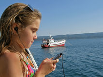 Girl enjoys the music. Wet girl with closed eyes enjoy in listen music on cell near the fishing boat on sea Royalty Free Stock Images