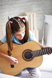 Girl enjoys playing the guitar Royalty Free Stock Photo