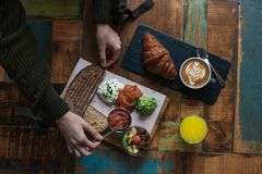 Delicious breakfast board on wooden tray. Girl enjoys and prepares to eat delicious natural healthy breakfast or sunday brunch at cafe or restaurant, hipster Royalty Free Stock Photos