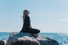 Girl enjoys the rays of the sun in a lotus pose. A girl enjoys the rays of the sun in a lotus position sitting on a stone on a background of the sea in black Royalty Free Stock Photo