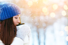 Girl enjoys the snow falls. Young woman drinking tea in the forest during a snowfall. Enjoying nature, wintertime Stock Image