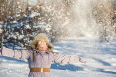 Girl enjoys the snow. Winter holidays in a fairy tale. Sun and snow. Happy girl in a fur hat Royalty Free Stock Photo