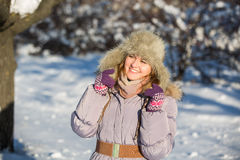 Girl enjoys the snow. Winter holidays in a fairy tale. Sun and snow. Happy girl in a fur hat Stock Photos