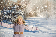 Girl enjoys the snow. Winter holidays in a fairy tale. Sun and snow. Happy girl in a fur hat Royalty Free Stock Images