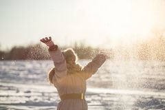 Girl enjoys the snow. Winter holidays in a fairy tale. Sun and snow. Happy girl in a fur hat Stock Photo