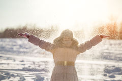 Girl enjoys the snow. Winter holidays in a fairy tale. Sun and snow. Happy girl in a fur hat Royalty Free Stock Image