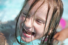 Girl enjoys summer day at the swimming pool. Stock Image
