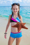Girl enjoys summer day at the tropical beach. Royalty Free Stock Photo