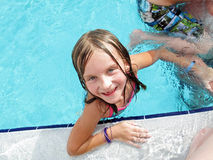 Girl enjoys sunny day at swimming pool. Royalty Free Stock Photography