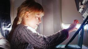 A girl enjoys the tablet in the aircraft.  stock video footage