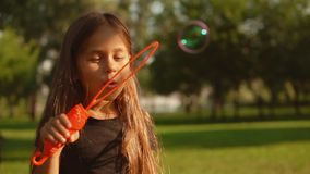 Little kid is blowing soap bubbles. Girl enjoys time outdoors. Kid is holding orange bottle stock video