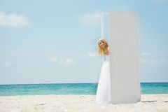 Girl entering open door on beach Royalty Free Stock Photo
