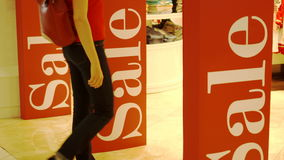 Girl entering shop. Three sales signs on shop entrance magnetic gates. Promotion. Consumerism concept. Girl entering shop. Three big red sales signs on shop stock video footage