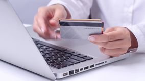 Girl enters data of three credit cards and completes online shopping. Close up stock footage