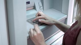 PIN code in the ATM. The girl enters her PIN code in the ATM stock footage