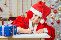 The girl with enthusiasm draws a Christmas card. Four-year girl dressed in a red suit Santa Claus draws pencils are in a festive Christmas interior royalty free stock image