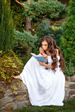 Girl with enthusiasm reads book. Lovely girl with enthusiasm reads the interesting book. She holding a book and an apple in his hand royalty free stock images