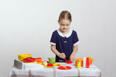 Girl enthusiastically cuts tomato Royalty Free Stock Photography