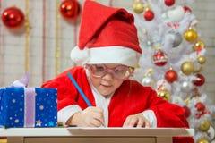 Girl enthusiastically prepares a gift card for Christmas Stock Photo