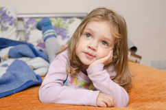 Girl enthusiastically watching TV. A girl laying on the couch and enthusiastically watching TV Stock Photography