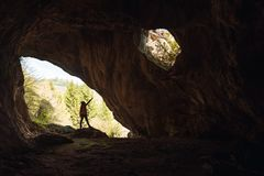 Girl in the entrance of a cave. Girl exploring the entrance of a cave rock hiking silhouette alone cat hiker outdoor light nature travel samar serbia landscape stock image