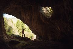 Girl in the entrance of a cave. Girl exploring the entrance of a cave rock hiking silhouette alone cat hiker outdoor light nature travel samar serbia landscape stock photography