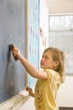 Girl Erasing Writing on Blackboard. Young female student erasing math problems from blackboard. Vertically framed shot Stock Photography