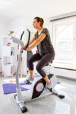 Girl on a ergometer Royalty Free Stock Images