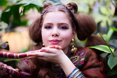 Girl in ethnic clothes in tropical garden with snake Stock Photography