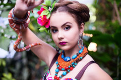 Girl in ethnic clothes in tropical garden with snake Stock Photo