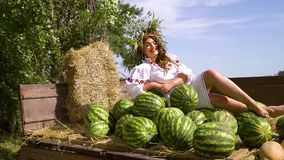 Girl in ethnic dress sitting in trailer with harvest outside. Pan of attractive brunette in ethnic dress and flower circlet sitting in old trailer with harvested stock video
