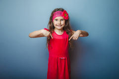 Girl European appearance haired child of seven in. Red bright dress shows thumb down on the gray background, direction royalty free stock images