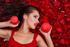 Girl of European appearance lies in red petals, holds candle lights near the face. stock photos
