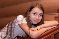 A girl of European appearance rests on a wooden staircase in a log house. stock photography