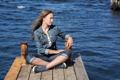 A girl of European appearance is sitting on a wooden pier. Summer day. Developing hair stock photos