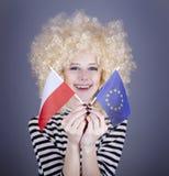 Girl with European Union and Poland flag. Beautiful girl with ringlets show European Union and Poland flag. Studio shot Stock Photography