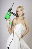 Girl in evening dress with a drill Stock Image