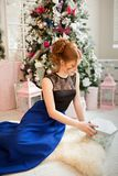 A girl in an evening dress opens a gift for the new year. New Year`s Eve. Christmas. A girl in a blue evening dress sitting next to a Christmas tree Royalty Free Stock Images