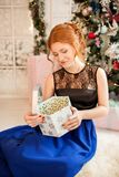 A girl in an evening dress opens a gift for the new year. New Year`s Eve. Christmas. A girl in a blue evening dress sitting next to a Christmas tree Stock Photo