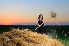 The girl in an evening dress with a pitchfork near a haystack Stock Images