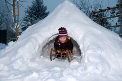 Girl in the evening in an igloo. Girl on the sled in self-built igloo in the winter dusk Royalty Free Stock Image