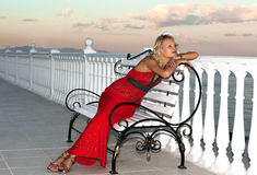 Girl in evening red dress sitting on a bench royalty free stock image