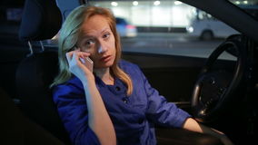 Girl in the evening talking on the phone while sitting in the car stock footage
