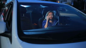 Girl in the evening talking on the phone while sitting in the car stock video