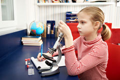 Girl examines drug for the microscope Stock Images