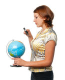 Girl examines the globe through a magnifier Stock Photo