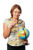 Girl examines the globe through a magnifier Royalty Free Stock Photo