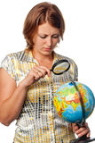 Girl examines the globe through a magnifier Stock Photos