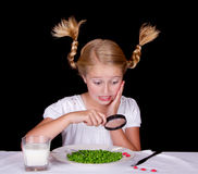 Girl examining bugs on table with magnifying glass Stock Photography
