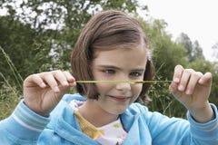 Girl Examining Caterpillar On Grass Stock Image